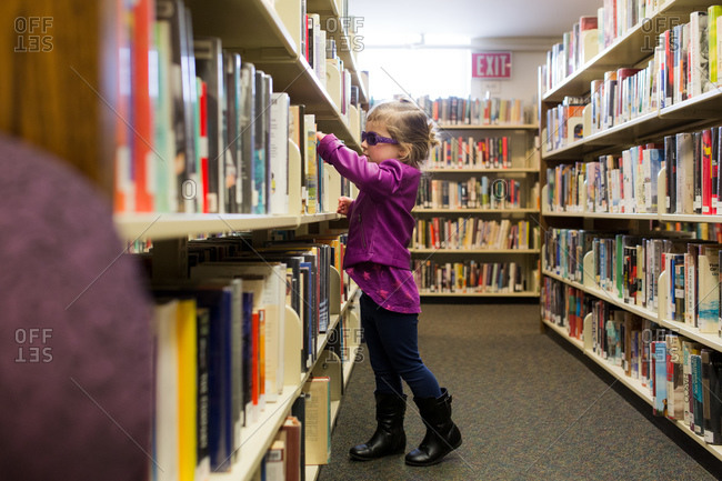 Girl browsing library shelf for books