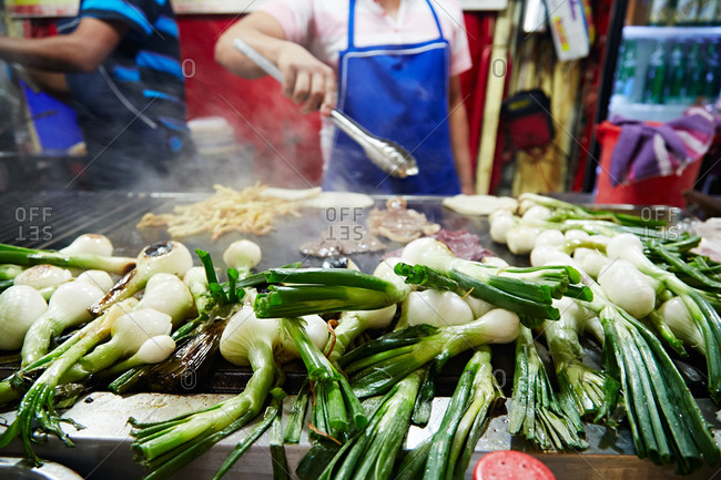 Onions, French fries and meat grilling in a commercial kitchen