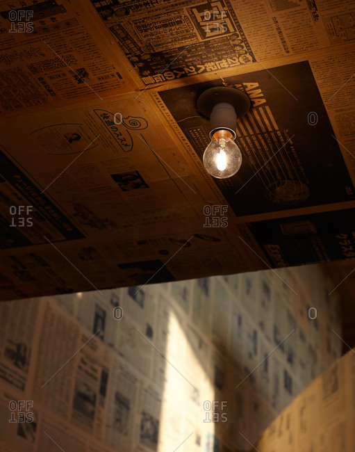 A dim light bulb attached to the ceiling of a newspaper-lined room