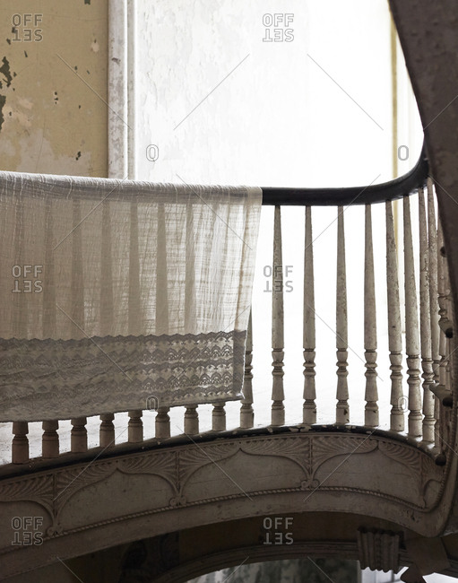 A lace tablecloth hangs over a banister