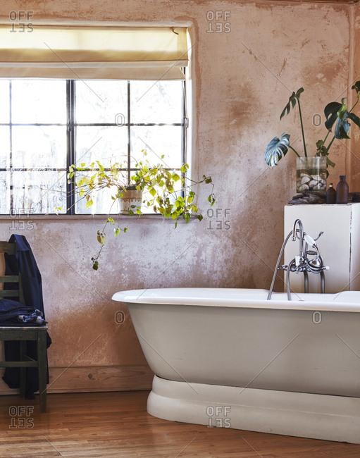 A freestanding bathtub in an adobe home