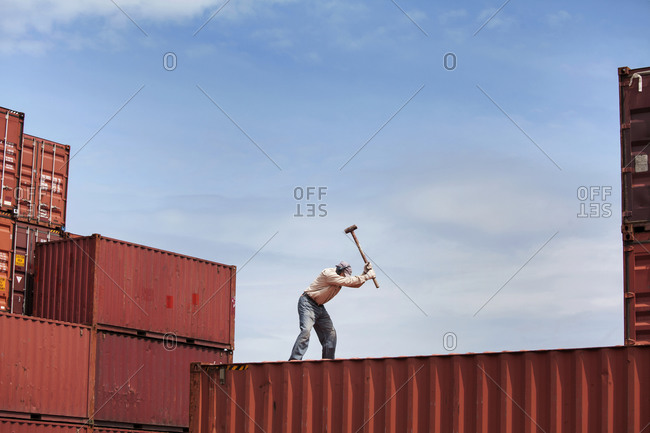 Man using sledgehammer on freight container