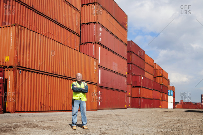 Employee with arms crossed in front of freight containers