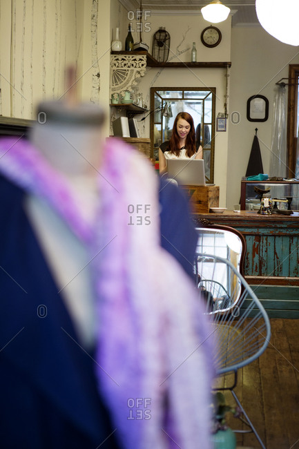 Female boutique owner using laptop in shop