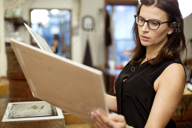 Woman comparing photographic prints in boutique