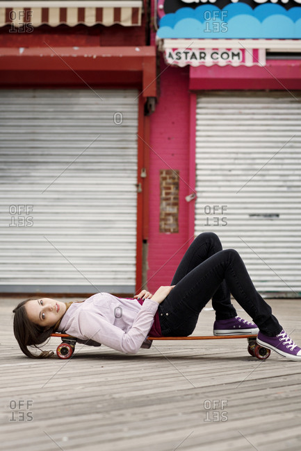 Young woman lying on skateboard