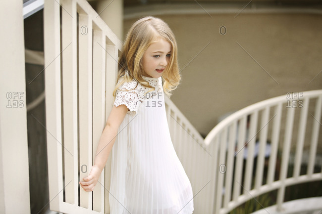 Young girl grabbing stair railing staring off