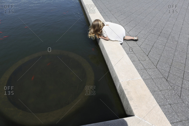 Young girl looking into koi pond