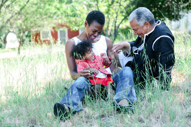 Little girl in a meadow with her mother and grandmother