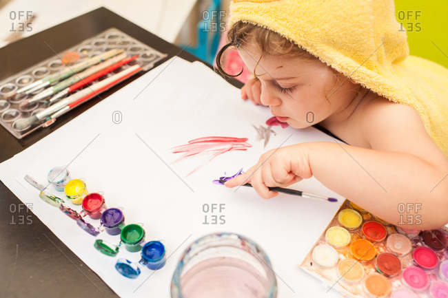 Young girl painting on a paper