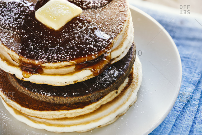 Stack of multi-grain pancakes with maple syrup and a blot of butter