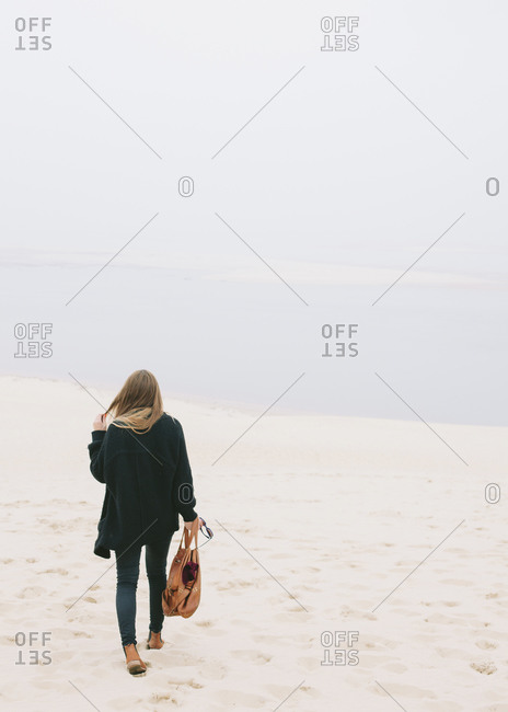 Back view of woman walking at the Dune of Pilat, France