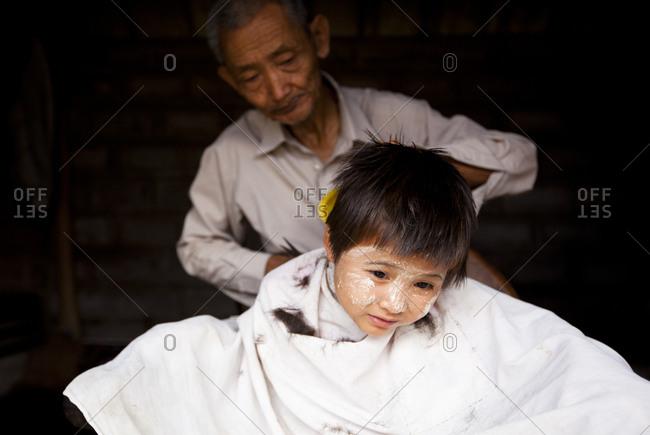 Nyaung Shwe, Myanmar - August 19, 2011: Child getting haircut in Myanmar