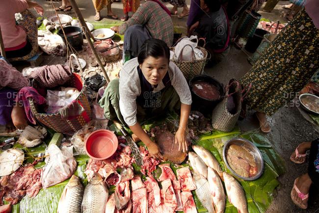 Nyaung Shwe, Myanmar - August 19, 2011: Fishmonger preparing fish in Nyaung Shwe Market, Myanmar