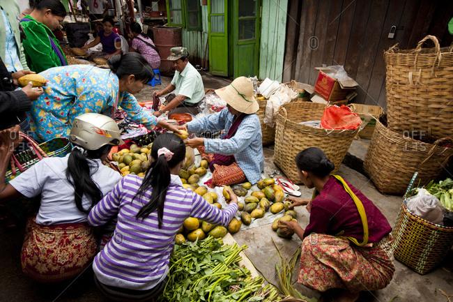 Nyaung Shwe, Myanmar - August 19, 2011: Women buying vegetables and fruit in Nyaung Shwe Market. Myanmar