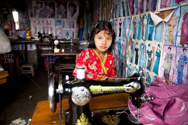 Nyaung Shwe, Myanmar - August 19, 2011: Child seamstress at Nyaung Shwe Market, Myanmar