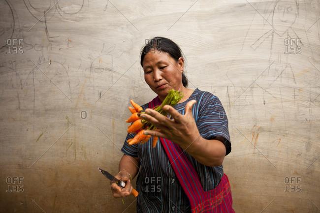 Nyaung Shwe, Myanmar - August 19, 2011: Woman preparing carrots at Nyaung Shwe Market, Myanmar