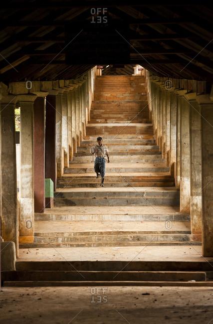 Inle Lake, Shan State, Myanmar - August 20, 2011: Man descending stairs of Thaung Tho Kyaung, Inle Lake, Myanmar