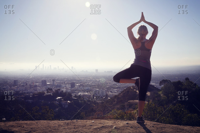 Woman in yoga pose overlooking city