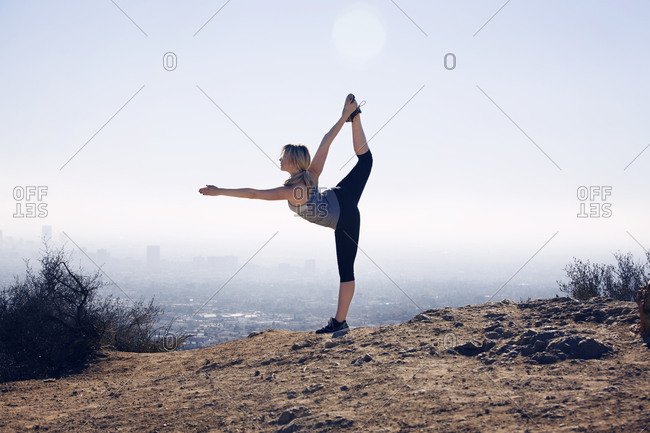 Woman in yoga position overlooking city