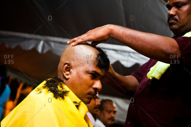 Gombak, Malaysia - January 20, 2011: Man having head shaved during kavadi festival