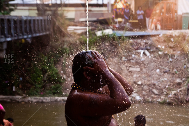Man showers and prays during kavadi festival