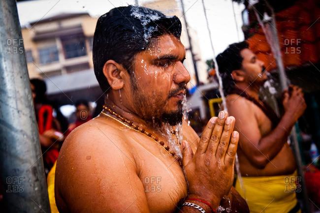 Gombak, Malaysia - January 20, 2011: Man showering at kavadi festival
