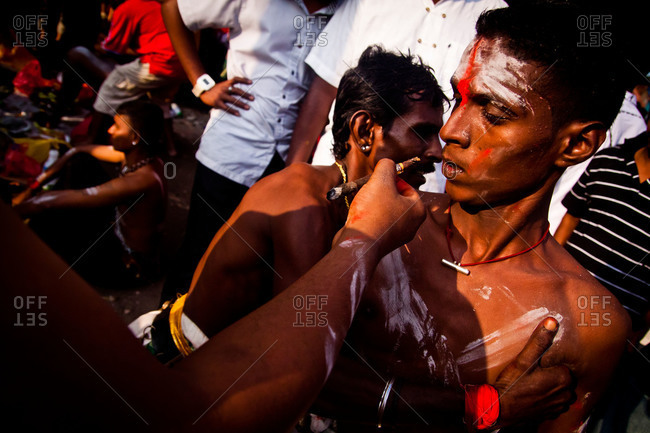 Gombak, Malaysia - January 20, 2011: An entranced man accepts cigar in Kavadi festival