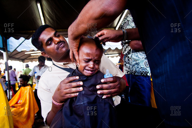 Gombak, Malaysia - January 20, 2011: Girl upset as her head is shaved during kavadi festival