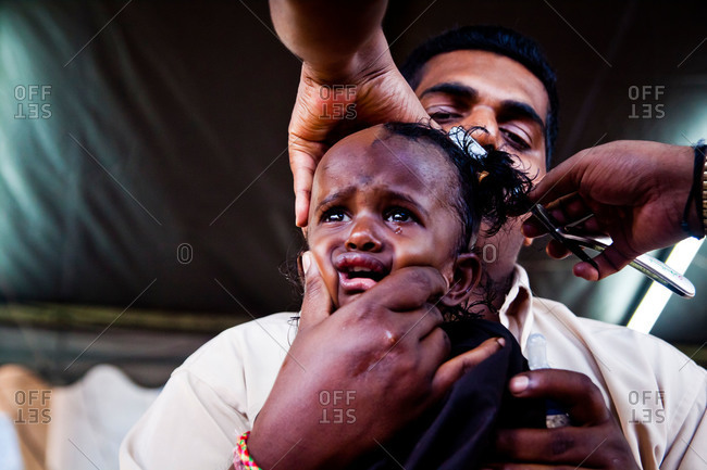 Gombak, Malaysia - January 20, 2011: Girl getting head shaved during kavadi festival