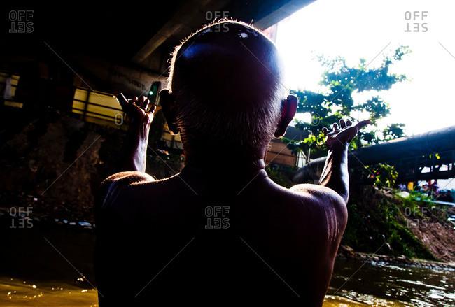 Man prays at the riverside in kavadi festival