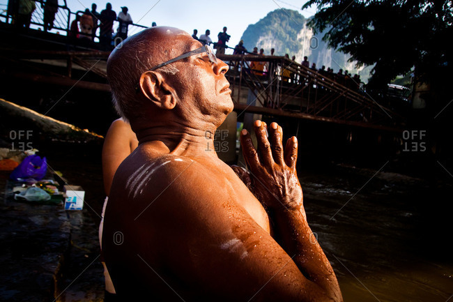 Gombak, Malaysia - January 20, 2011: A man prays at the riverside in kavadi festival