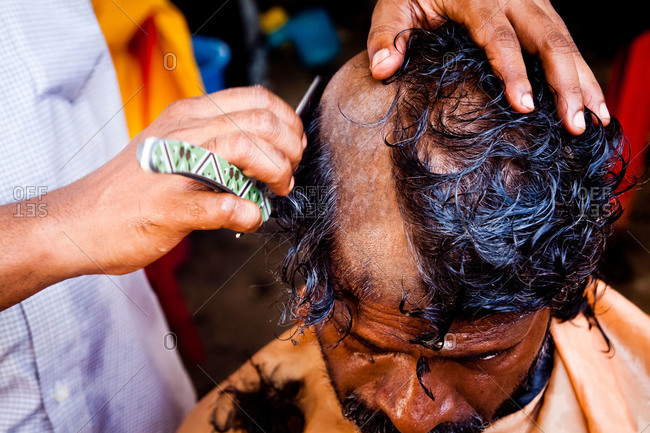 Gombak, Malaysia - January 20, 2011: A man has his head shaved for kavadi festival
