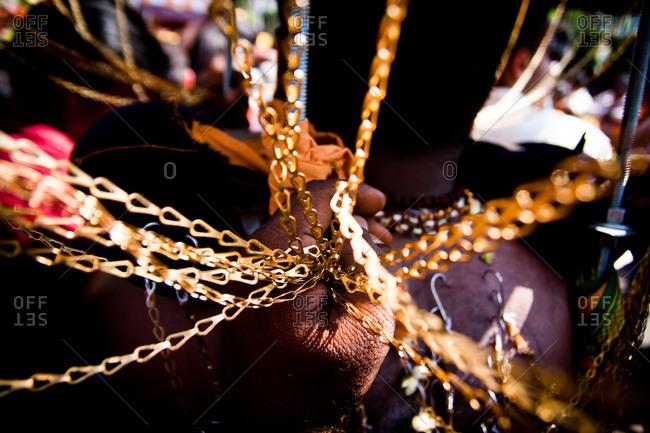 Golden kavadi chains in hand