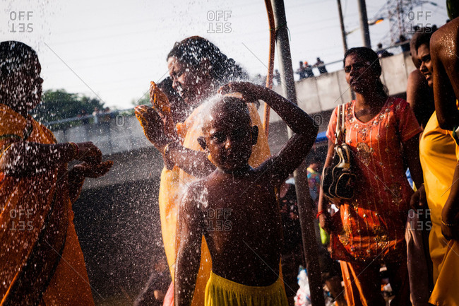 Gombak, Malaysia - January 20, 2011: A boy showers by river during kavadi festival