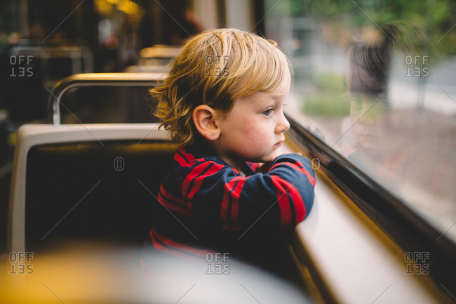 Little boy staring out the window of a train