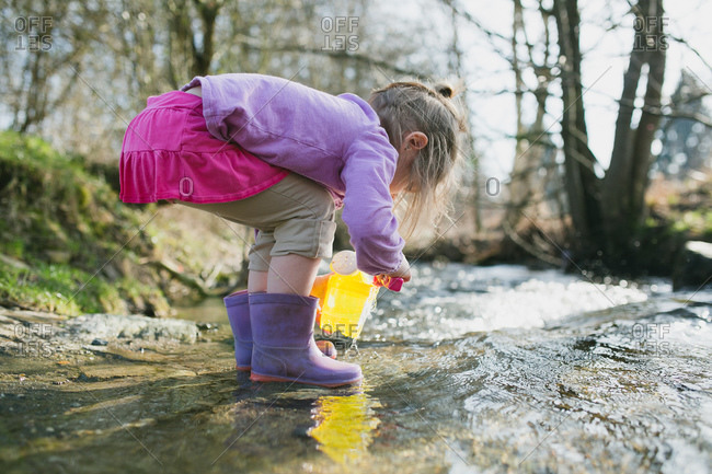 A little girl plays in a stream