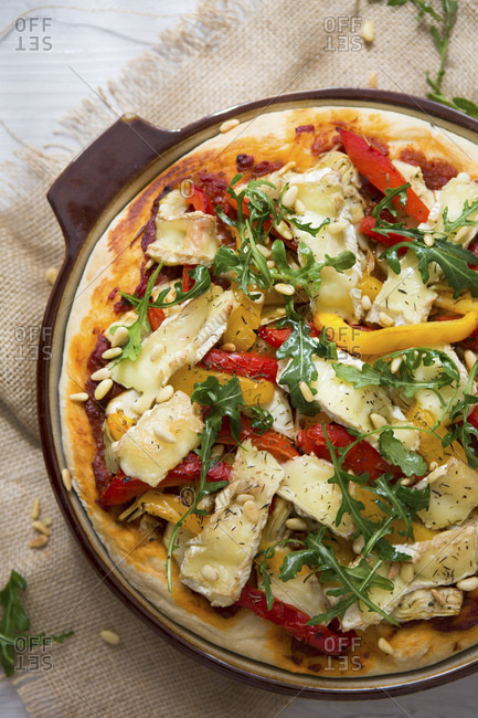Homemade vegetarian pizza with peppers, brie and arugula