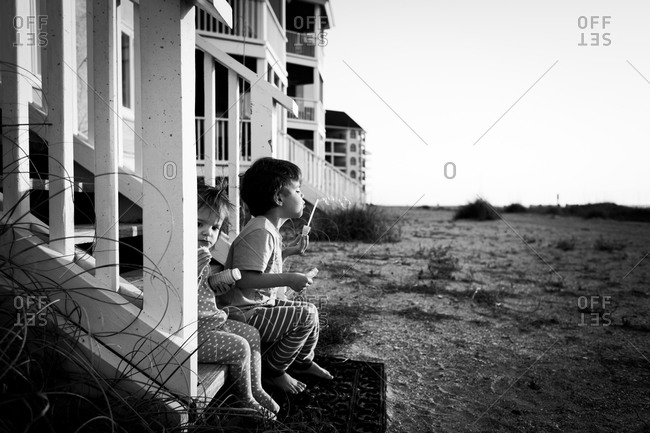 Two children sit on the steps of a beach house