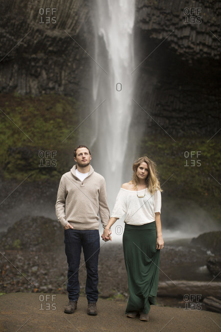 A couple looks in different directions standing in front of a waterfall