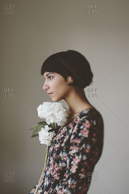 A woman holds flowers to her chin