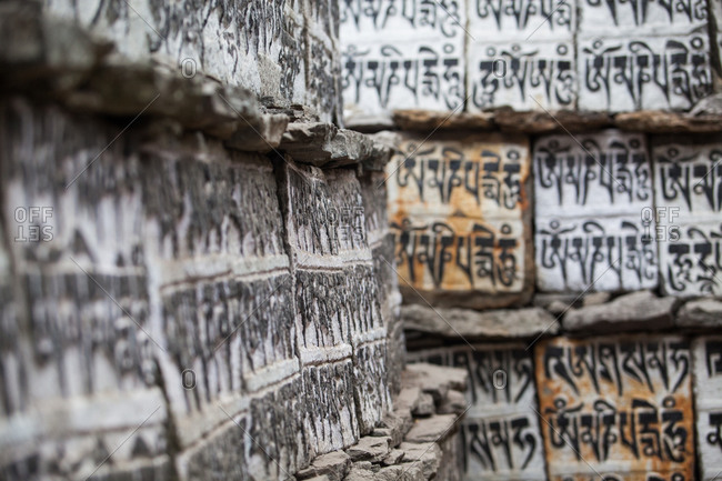 Buddhist prayer inscriptions on a wall in the village of Lukla, Nepal