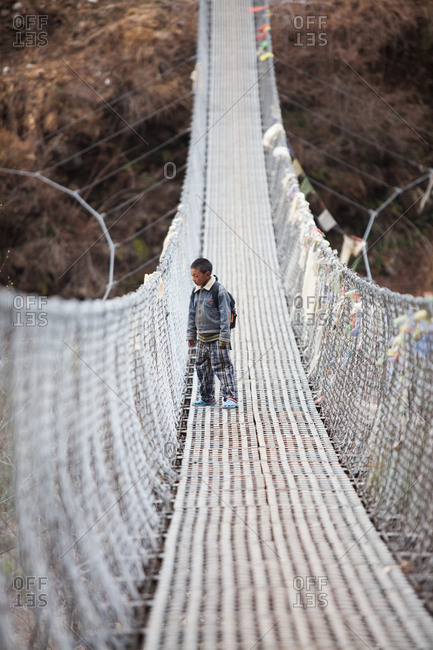 Boy standing on a suspension bridge in Nepal