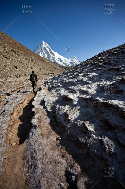 Man trekking towards Mount Everest Base Camp after leaving the tiny village of Gorek Shep in the Himalayas, Nepal