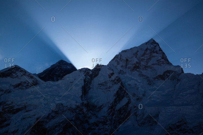 Beam of light shining from behind Himalayan peaks in Nepal