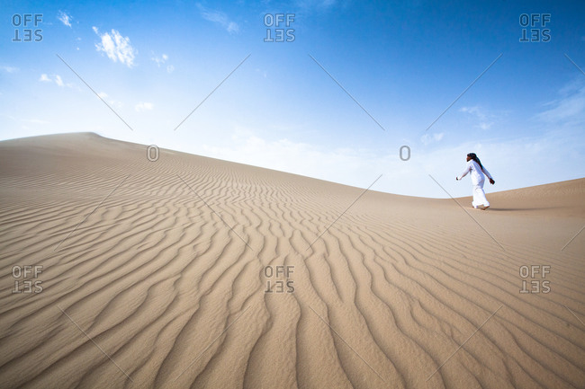 Lone man walking in the Sahara desert