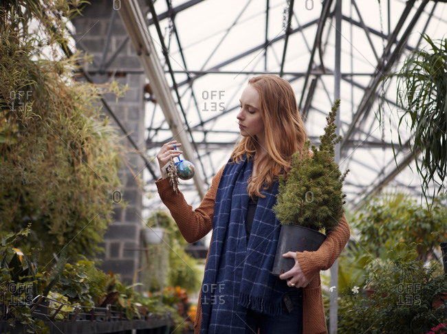 Woman in plant nursery looking at ornament