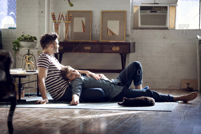Gay couple lounging in loft with cat