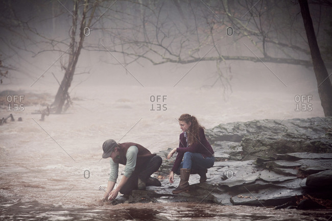 Couple kneeling by river to wash hands