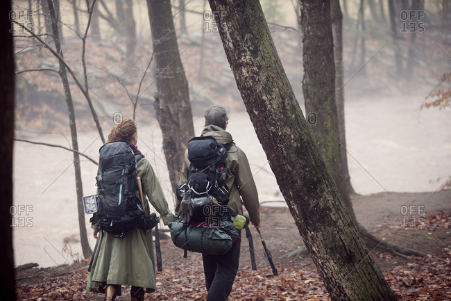 Young couple walking in woods with backpacks